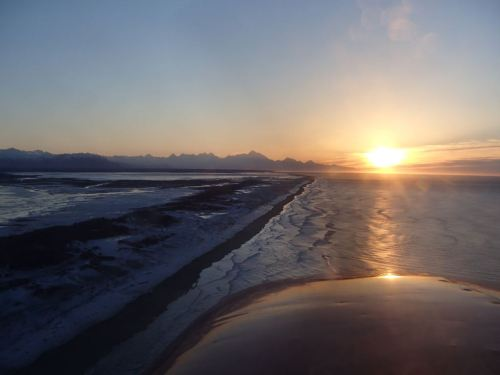 Flying down the coast at sunset,  with ice along the shore